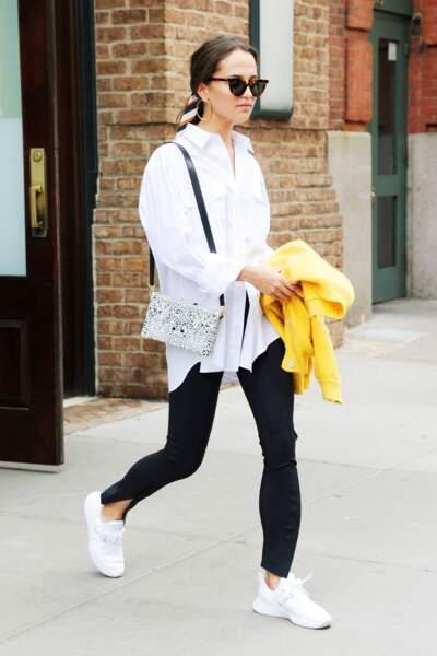 Alicia Vikander mise sur une tenue casual avec une chemise blanche ample et longue, entrouverte, un slim noir et des baskets blanches