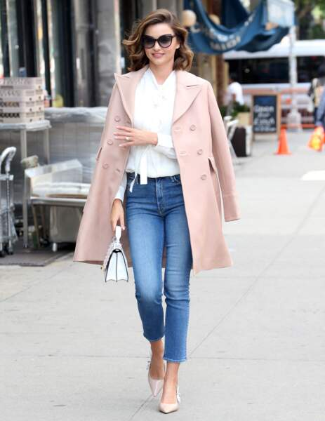 La top modèle Miranda Kerr mise sur un look très élégant avec une chemise blanche ajustée, un jean taille haute, des escarpins rose pâle assortis à son manteau et un sac blanc Fendi,