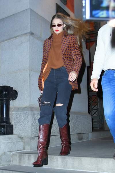 À New-York, Gigi Hadid réchauffe le bas ses jambes et rentre son jean dans ses bottines hautes.