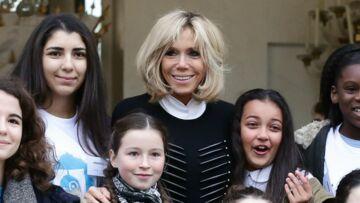 Photos – Brigitte Macron en pull long, jupe courte et bottes pour recevoir les enfants de l'Unicef à l'Elysée