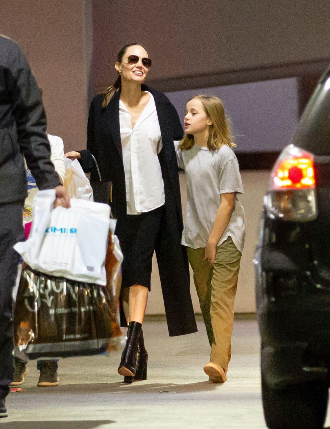 Angelina Jolie aperçue avec son fild Knox en août 2019 revisite la chemise blanche qu'elle porte avec une jupe mi-longue et une longue veste noire