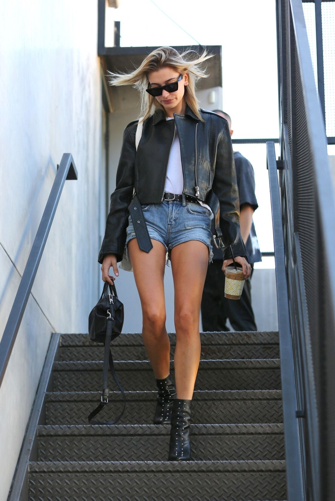 Hailey Baldwin en perfecto noir associe cette veste à une paire de jean ou de short en jeans flare, des talons ou des bottines et une paire de solaires noires