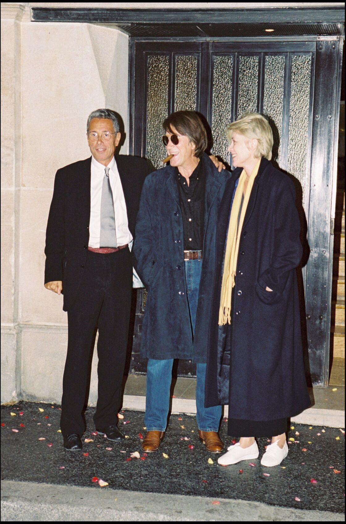 Le maxi pardessus de Françoise Hardy avec Jacques Dutronc et Jean-Marie Périer lors d'un vernissage de Perrier en 1990