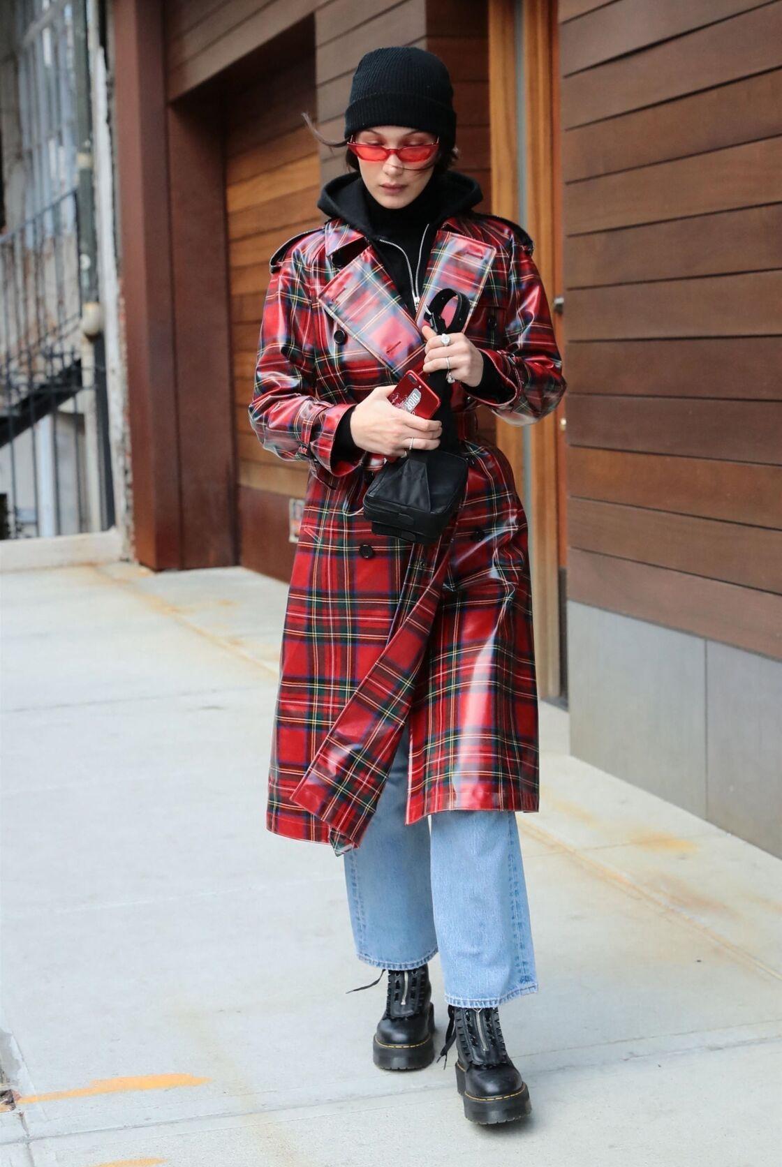 Bella Hadid dans les rues de New York ressort le trench écossais en vinyle et l'associe aux indétrônables  Dr. Martens noires