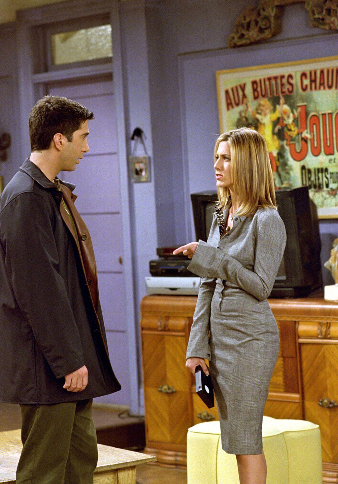 Tailleur gris et chemisier sous une veste de costume, les tenues fétiches de Rachel Green pour aller travailler.