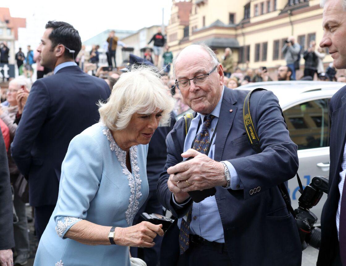 Arthur Edwards avec Camilla Parker-Bowles, à Leipzig, en mai 2019. Le photographe montre à l'épouse du prince Charles une photographie du petit Archie.