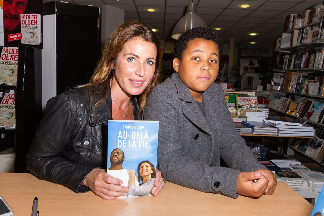 Sandrine Diouf, la veuve de Mouss Diouf, accompagnée de son fils Isaac, lors d'une séance de dédicaces de son livre, a Marseille, en 2014.