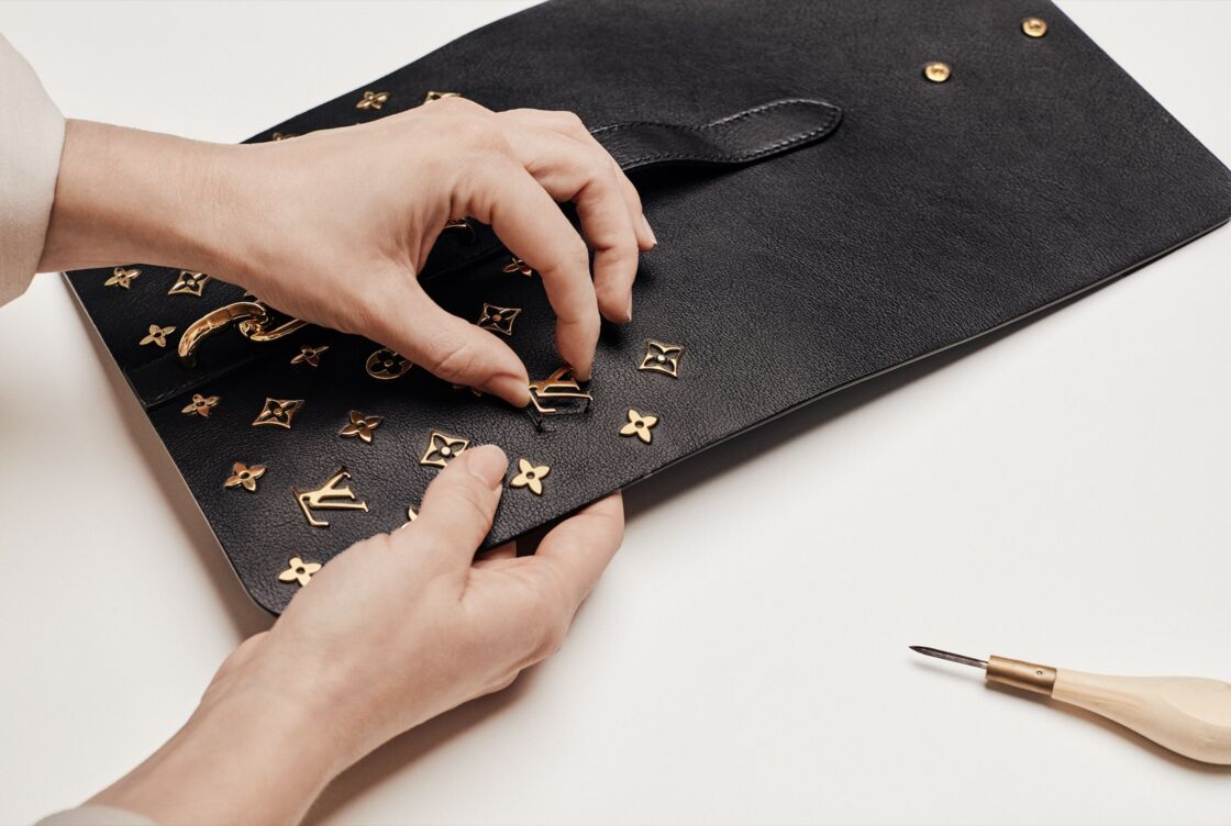 36 fleurs de Monogram et 4 « LV » en métal doré habillent le rabat du sac Rendez-Vous de Louis Vuitton.