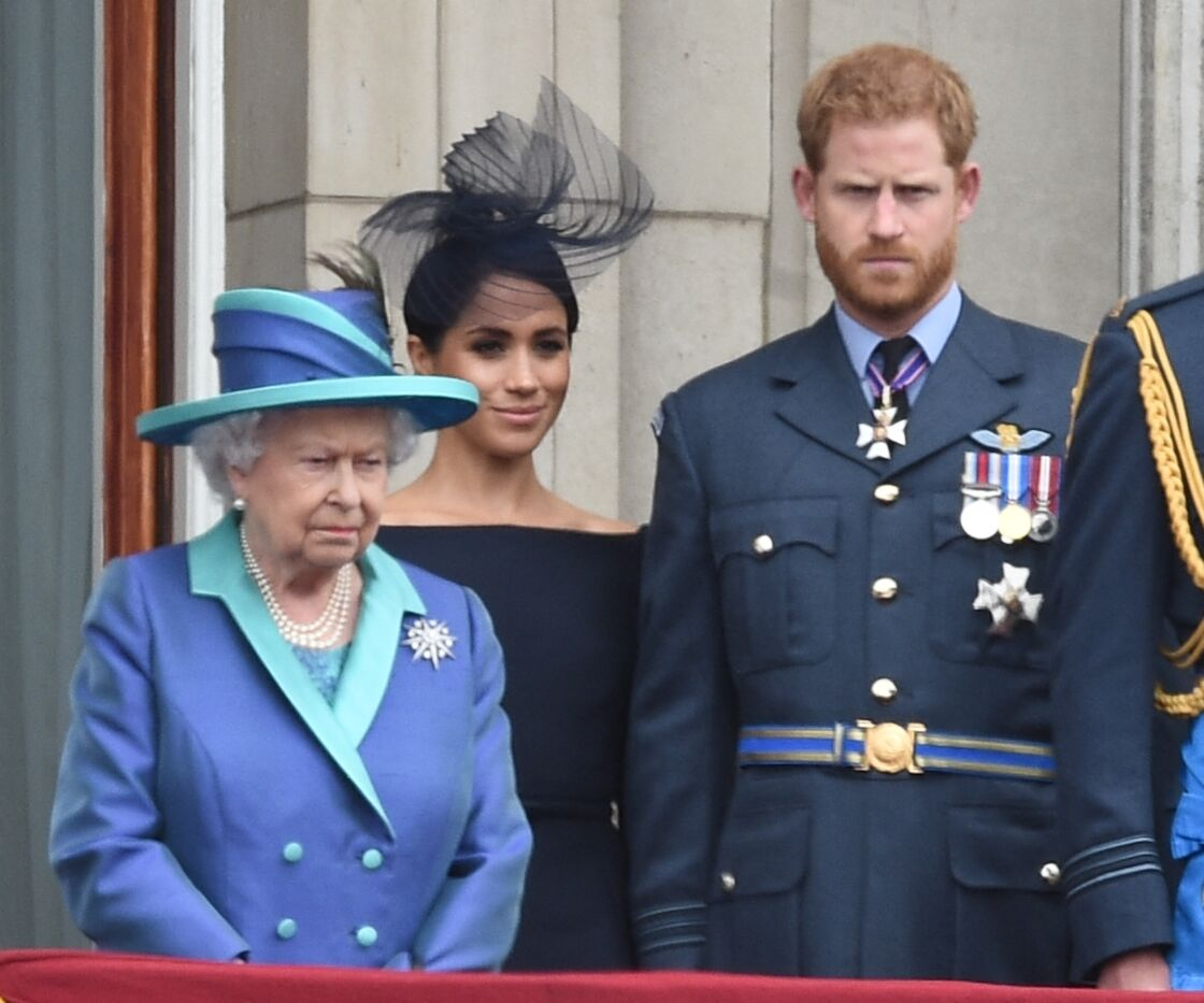 La reine Elizabeth II, Meghan Markle et le prince Harry lors du centième anniversaire au palais de Buckingham, le 10 juillet 2018, à Londres