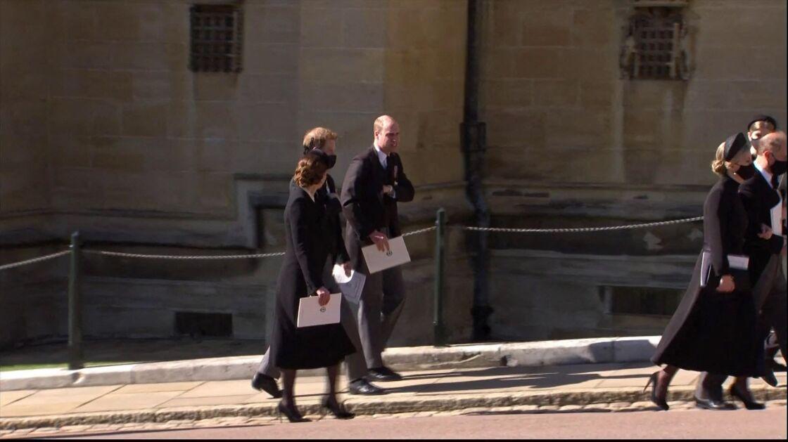 Le prince William et le prince Harry, accompagnés de Kate Middleton, à la sortie des funérailles du prince Philip, duc d'Edimbourg à la chapelle Saint-Georges du château de Windsor, Royaume Uni, le 17 avril 2021.