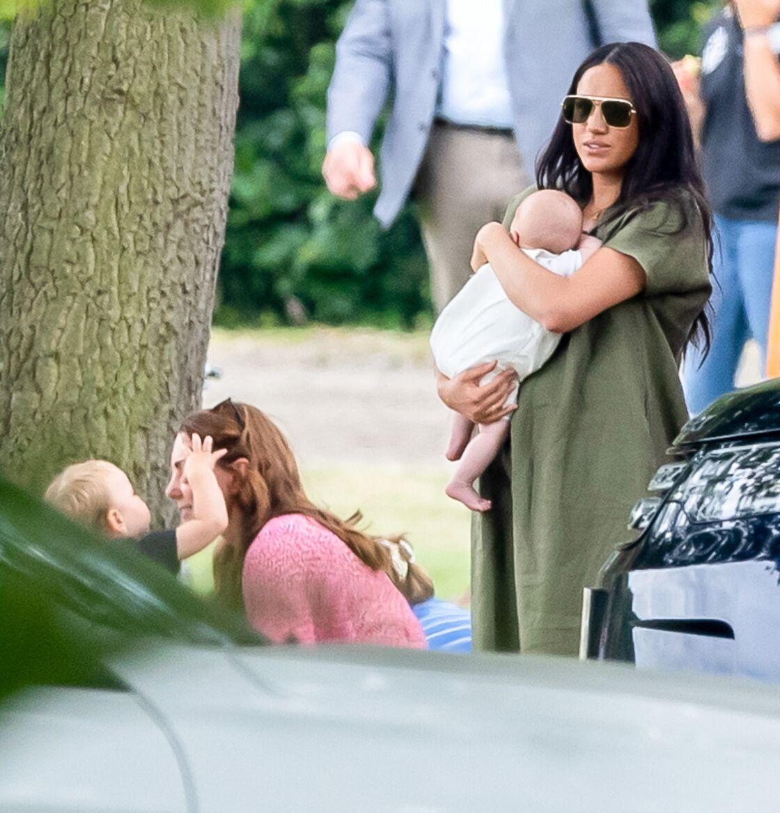 Le prince Louis sur le point de voler les lunettes de soleil de Kate Middleton (à gauche) et Meghan Markle avec le petit Archie