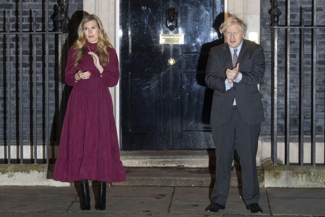 Le premier ministre Boris Johnson et sa compagne Carrie Symonds applaudissent devant le 10 Downing Street pour rendre hommage au capitaine Tom Moore, vétéran et héros du confinement décédé à l'âge de 100 ans. Londres, le 3 février 2021