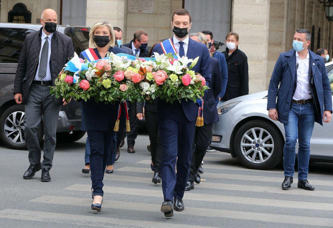 Marine Le Pen, au côté de Jordan Bardella (vice-président du Rassemblement national), dépose une gerbe au pied de la statue de Jeanne d'Arc, place des Pyramides, à Paris, le 1er mai 2021.