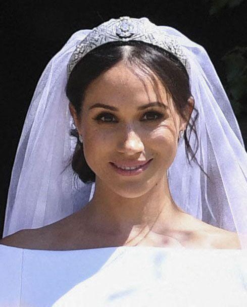 Dans son voile en tulle et organza, un bout de la robe bleue qu'elle portait lors de son premier rendez-vous avec le prince Harry