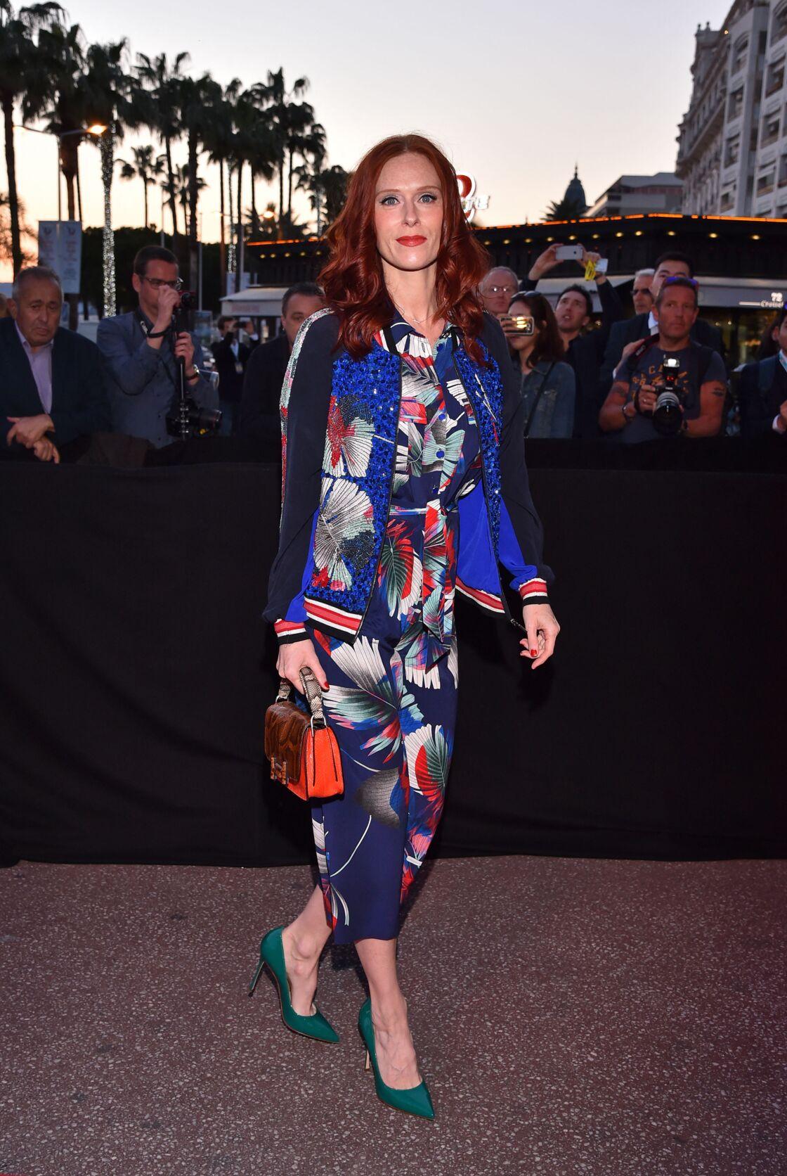Audrey Fleurot fait sensation à Cannes dans une combinaison florale et tropicale nuancée de bleu, rouge et blanc. L'actrice accessoirise sa tenue estivale à des escarpins turquoises et un sac à main orange.