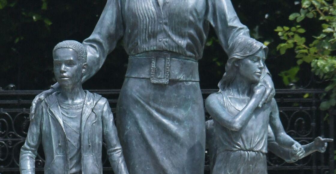 Trois enfants entourent la princesse Diana (le troisième est caché derrière la petite fille)
