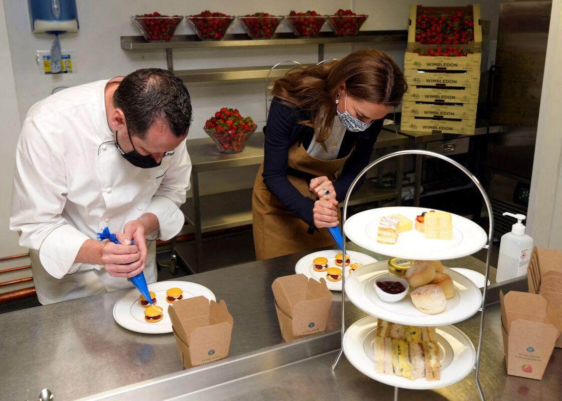 Kate Middleton aide à préparer des desserts aux fraises avec le chef Adam Fargin dans les cuisines du All England Lawn Tennis and Croquet Club de Wimbledon à Londres, le 2 juillet 2021.