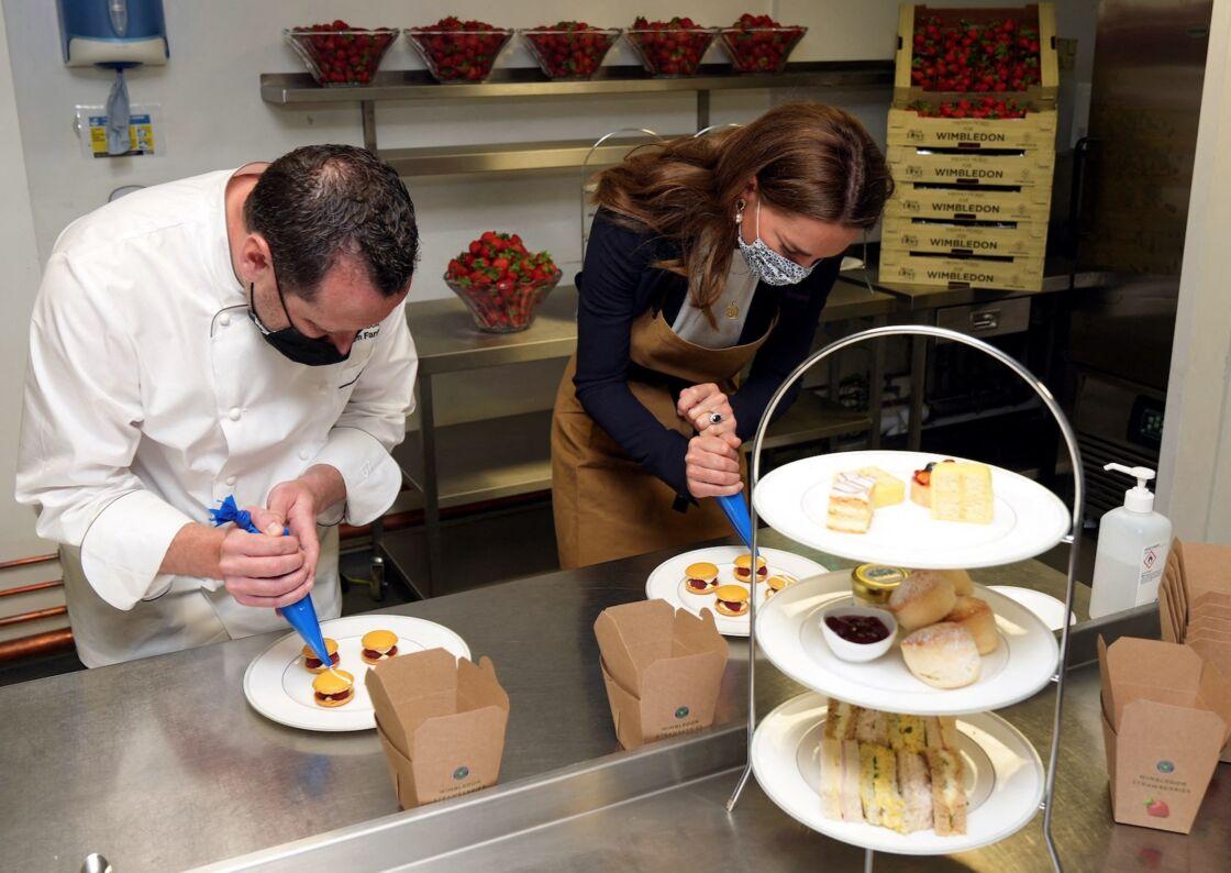 Kate Middleton prépare les desserts aux fraises en compagnie du chef Adam Fargin dans les cuisines du all England Lawn Tennis and Croquet Club de Wimbledon, à Londres, le 2 juillet 2021.