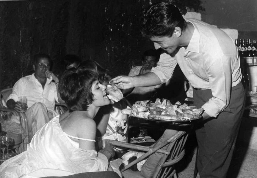 Virée en boîte de nuit, à Antibes en 1960. Sacha Distel nourrit l'actrice et speakerin française Noelle Noblecourt