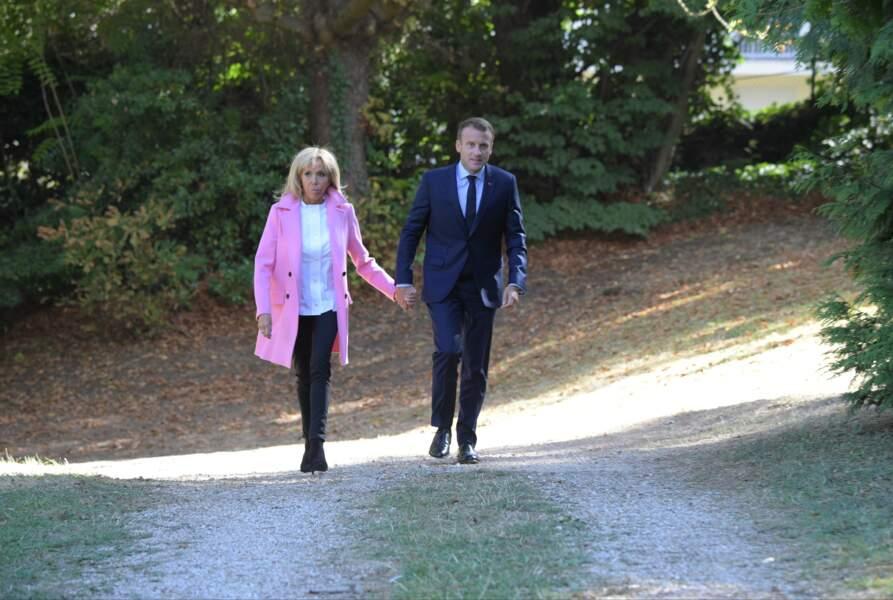 Look noir et blanc sous son manteau rose en cachemire signé Louis Vuitton, Brigitte Macron se distingue.