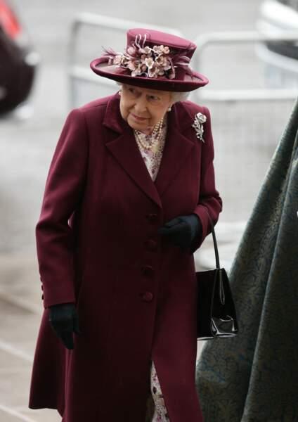 La reine Elizabeth II tout de bordeaux vêtue et d'un chapeau fleuri