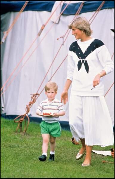 Lady Diana et son fils le prince Harry portant une assiette de fraises, lors d'un match de polo à Windsor en 1987