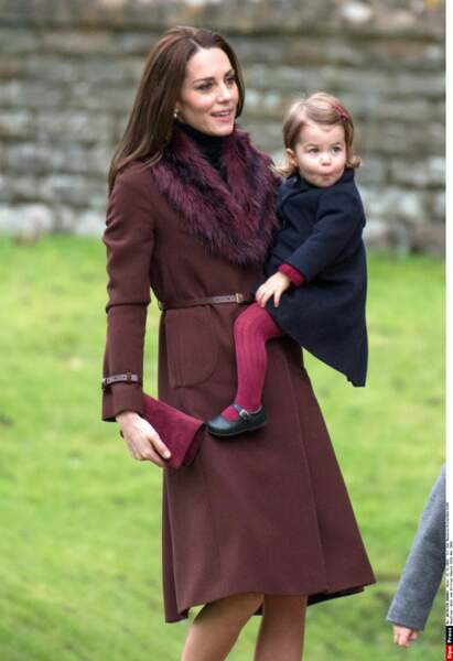 La mignonne Charlotte porte des collants grenats, Kate choisit donc une pochette en velour de la même couleur