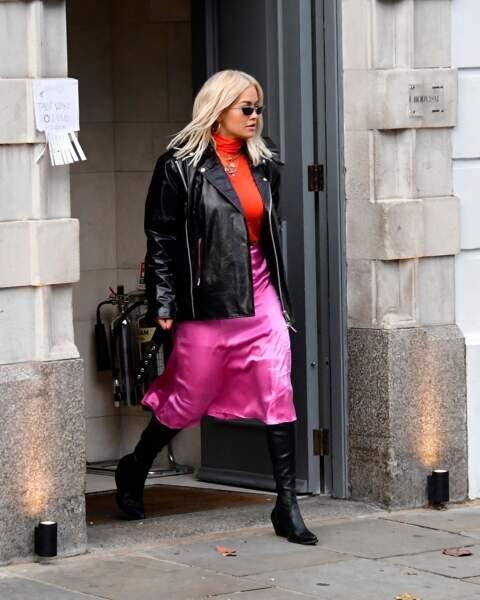 Rita Ora casse son look en satin acidulé avec une paire de santiags noires, assorties à son perfecto.