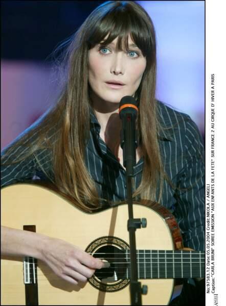 Cheveux raides et frange longue : la coiffure iconique de Carla Bruni, ici sur un plateau télé en 2004