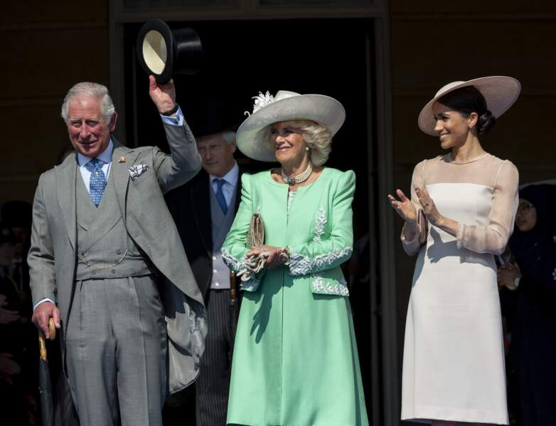 Charles salue la foule, avec Camilla et Meghan à ses côtés, lors de la garden party à Buckingham, le 22 mai 2018