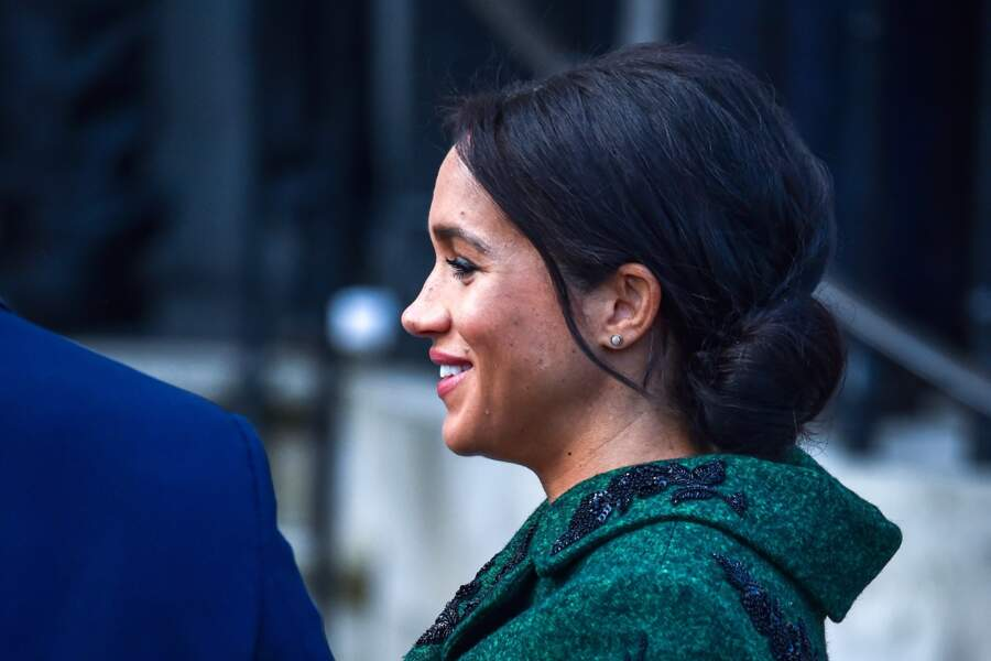 Meghan Markle porte un vrai chignon bas avec quelques mèches encadrant son visage le 11 mars 2019.