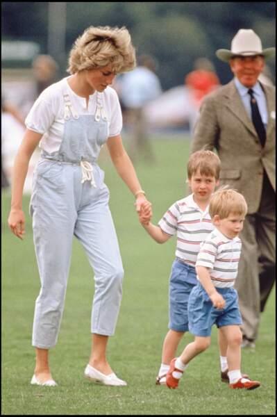 La princesse Diana, en salopette bleu ciel, et ses fils William et Harry, en bermudas et polos rayés, en 1987
