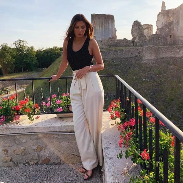 Camille Cerf, élégante en top noir et pantalon paper bag Mango, sur le Tour de France, en juillet 2019