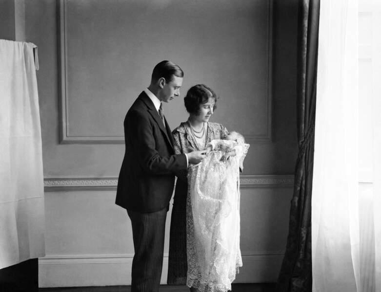 La reine Elizabeth lors de son baptême, accompagnée de la Reine Mère et du roi George VI, en mai 1926