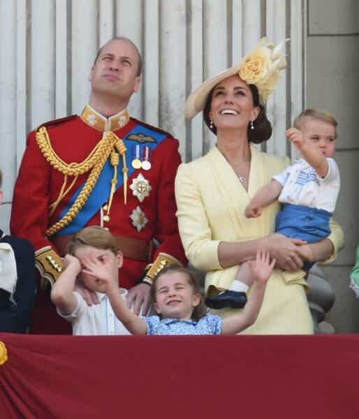 Le prince George se tenant la tête et la princesse Charlotte écartant les bras