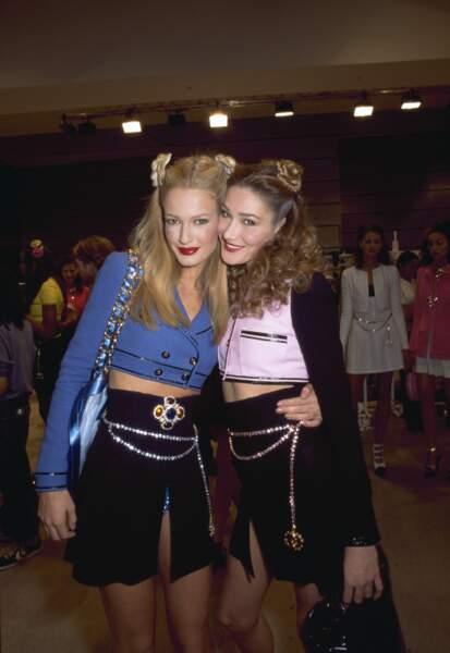 Cheveux ondulés et macarons, le look espiègle de Carla Bruni, avec Karen Mulder lors de la Fashion Week en 1994