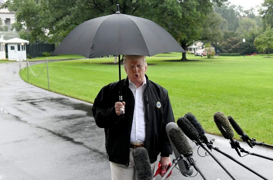 Donald Trump sous son parapluie répondant aux journalistes avant son embarquement