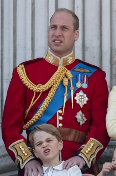Le prince George faisant la grimace et tenue par son père, le prince William de Cambridge