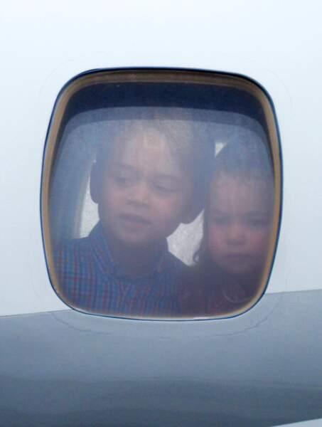 Le prince George et Charlotte regardent du hublot de l'avion
