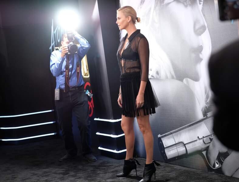Charlize Theron : en jupe courte et soutien-gorge griffé apparant