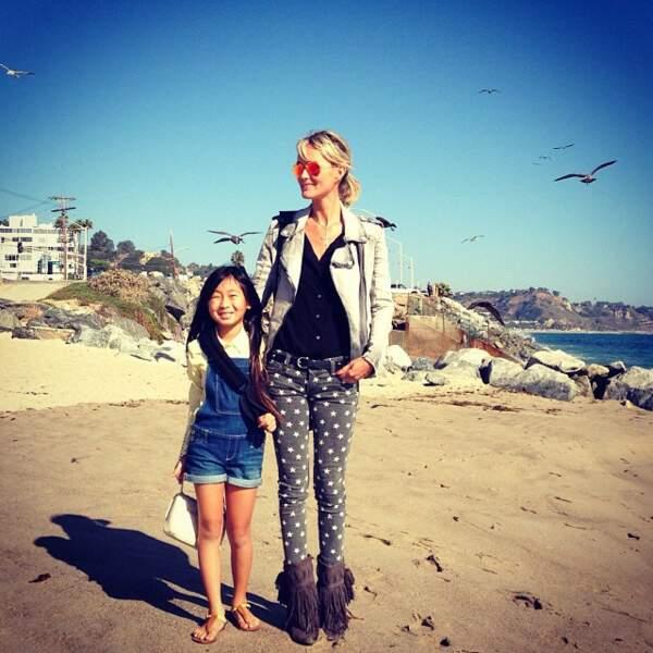 Laeticia Hallyday, en boots à franges et jean skinny étoilé, sur une plage de Malibu avec Jade en 2013