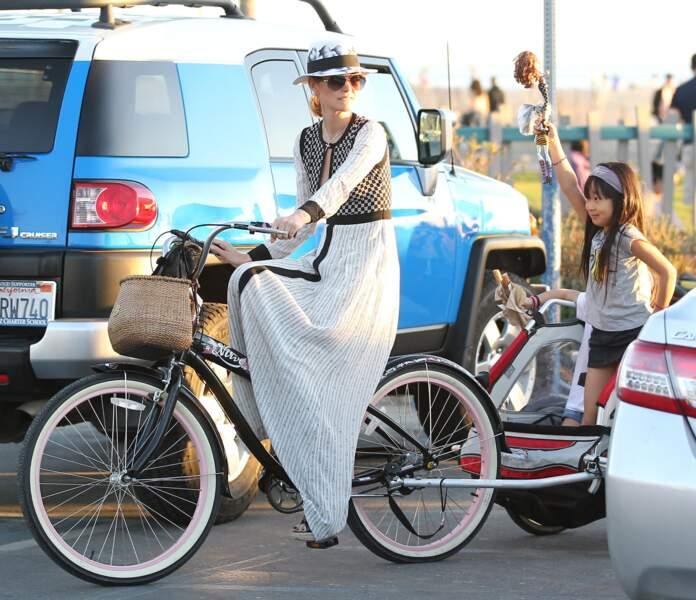 Laeticia Hallyday, en robe rayée extra longue, lors d'une balade à vélo à Santa Monica avec Jade en février 2013