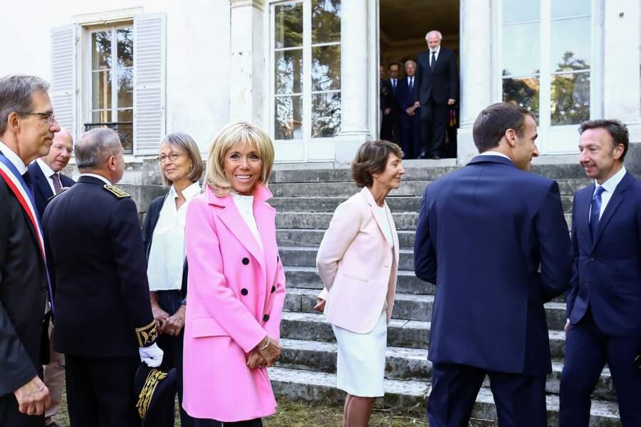 Lumineux, le manteau rose de Brigitte Macron fait ressortir son teint.