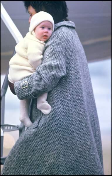 Le prince Harry dans les bras de sa nourrice Barbara Barnes, à l'aéroport d'Aberdeen en Écosse, en 1985