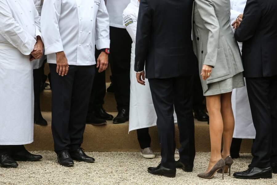 Brigitte Macron porte une robe zippée grise signée Louis Vuitton