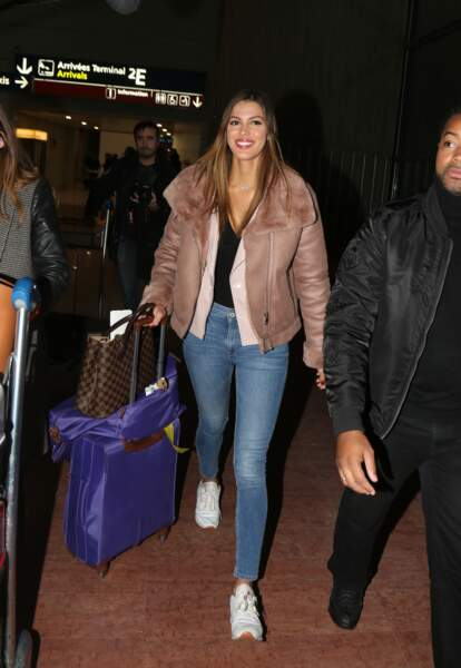 Iris Mittenaere porte un look décontracté mais féminin à l'aéroport. Jeans, basket et perfecto : un must !