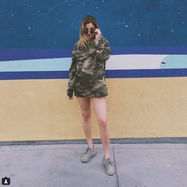 Plus street, Darina Scotti transforme le pull camouflage en robe courte avec des sneakers et lunettes de soleil.