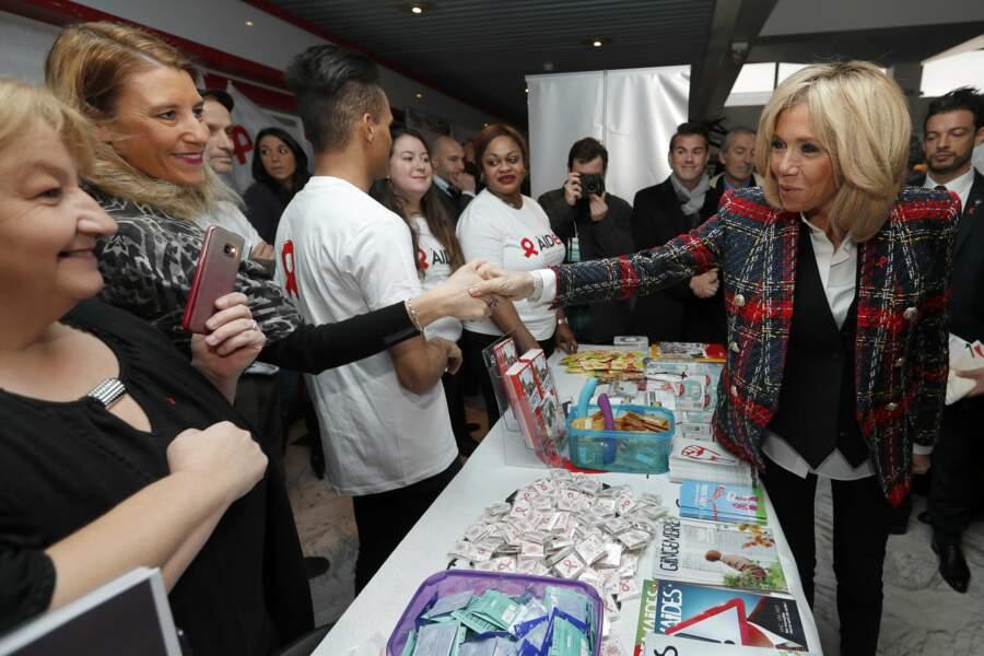 Brigitte Macron en veste de blazer avec les membres de l'association Aid's