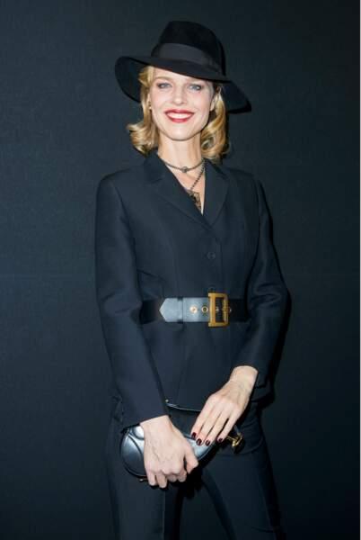 Eva Herzigova très élégante en tailleur ceinturé et chapeau feutré
