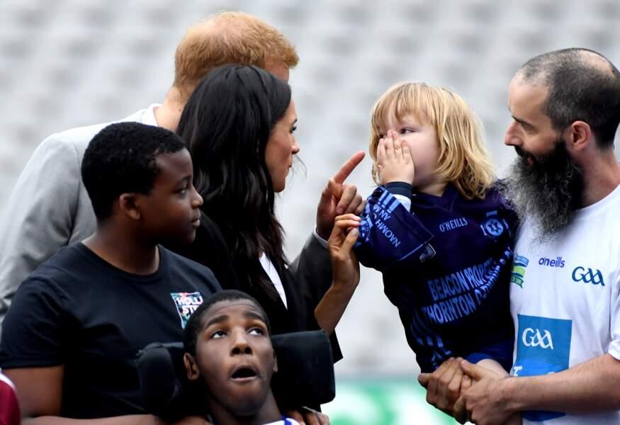 Meghan et Harry jouent avec un enfant